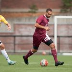 Willamette University men's soccer player kicks the ball