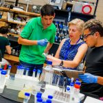 A New College of Florida professor works with students in a science lab