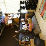 Eckerd College students visit in a residence hall room