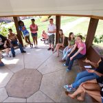 McDaniel College students and faculty talk together while sitting under a gazebo