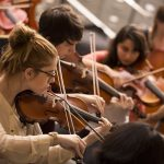 Southwestern University orchestra students play violins together