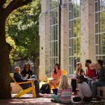 A Southwestern University professor and students enjoy class outside in the sunshine
