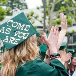 "Evergreen State College graduate wears a cap with the words ""Come as you are"" on it."