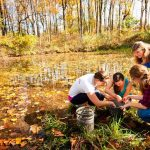 Goucher College students collect specimans from a pond