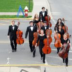 Juniata orchestra students walk across campus carrying their instruments