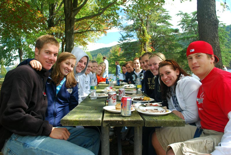 Juniata College students enjoy a meal together at a picnic table outdoors