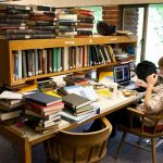 A Reed College student studies among stacks of books