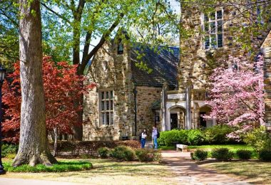 Students stand in front of a Rhodes College campus building on a fall day