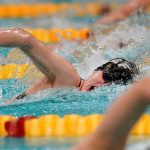 A St. Olaf student swims in a meet