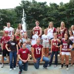 Austin College varsity athletes pose in front of a campus fountain