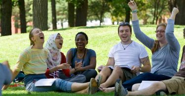 Beloit College students have a class on the campus lawn