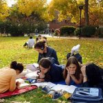 Clark University students study together on the campus lawn