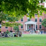 Earlham College students sit on the campus lawn