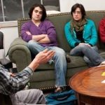 Kalamazoo College students sit together and talk in a residence hall