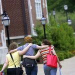 Hendrix College students walk arm in arm across campus