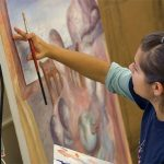 A Kalamazoo College student paints on canvas